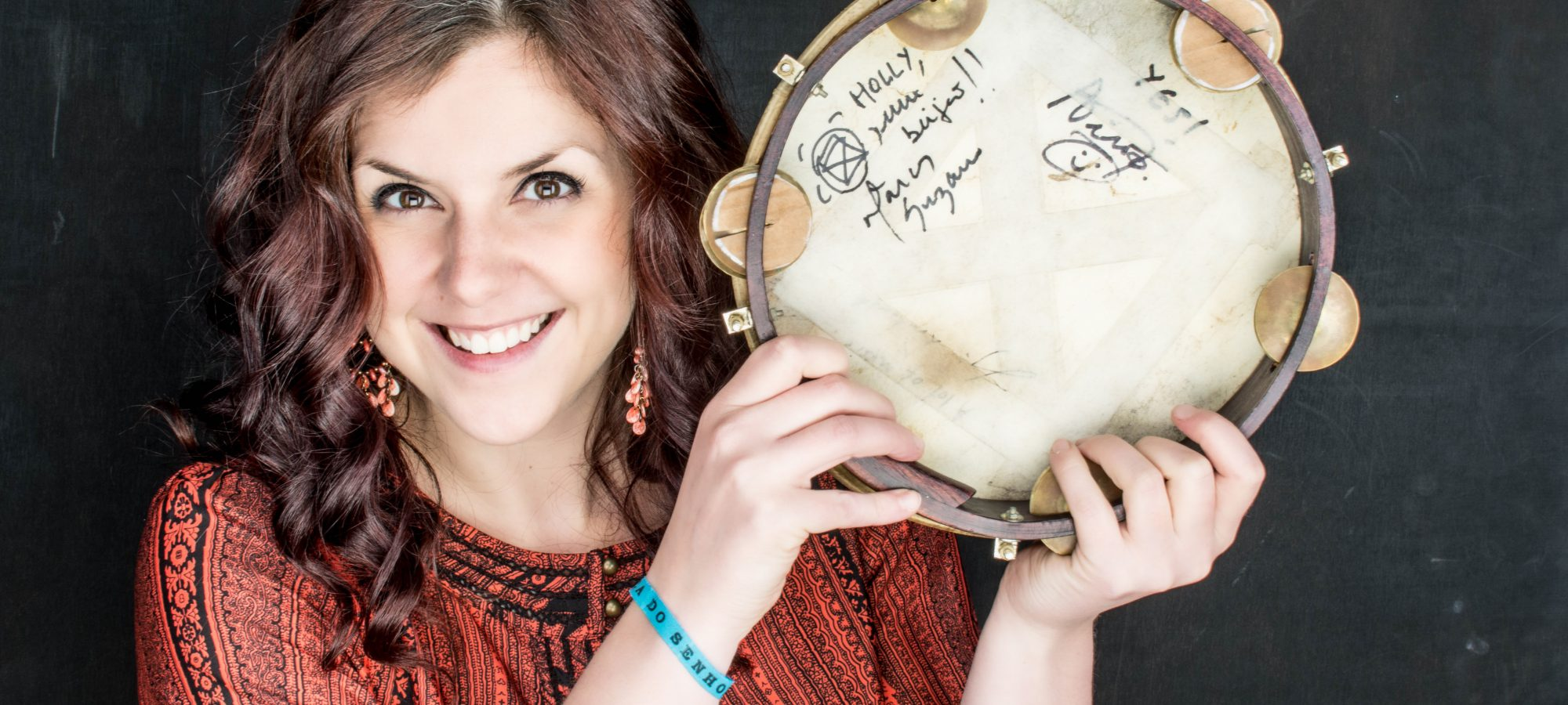 holly prest, artistic director, holding a pandeiro drum