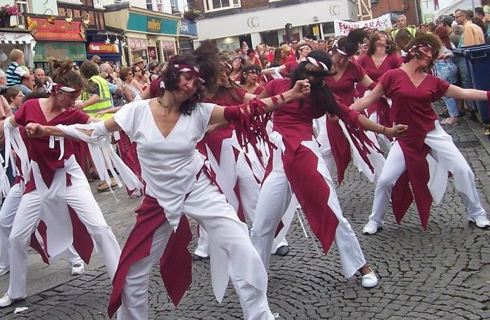 Group of dancers performing in the streets with a crowd watching