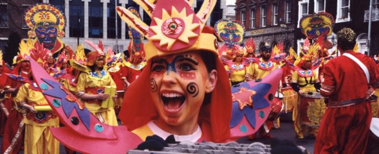 Facepainted Carnival performer smiling close up to the camera