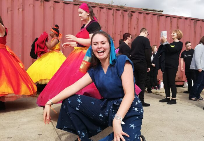 An image of Sally, a dance artist, crouching and smiling